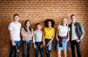 Group of teens/young adults against a brick wall after DBT skills class where they were learning interpersonal effectiveness skills at Balance and Potential Therapy in Alpharetta, GA 30022