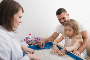 father and daughter play in sand tray with therapist during play therapy with a child counselor in Alpharetta, GA 30022