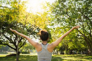 Young female runner stretching arms out to the sky while exercising in the park | Therapy for depression | help for depression | depression counseling | Alpharetta, GA | 30022